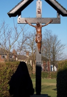 Praying before crucifix in garden